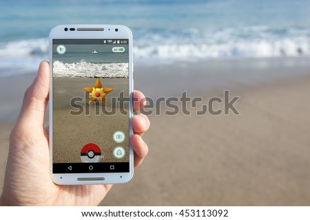 "SANTA CRUZ, CALIFORNIA - July 15, 2016: The hit augmented reality smartphone app ""Pokemon GO"" shows a Pokemon encounter at the beach. - stock photo"