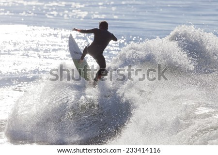 SANTA CRUZ, USA, NOVEMBER 25, 2014: Athlete surfing on Santa Cruz beach in California. November 25, 2014 - stock photo