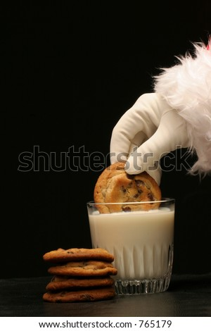 santa dips a cookie in the milk with pile of chocolate chip cookies on black background - stock photo