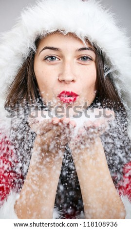 Santa girl blowing snow from her hand - stock photo