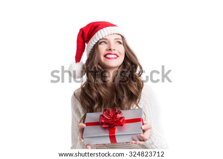 Santa girl holding christmas gift. Young happy woman in santa hat looking sideways showing Christmas present isolated on white background. - stock photo