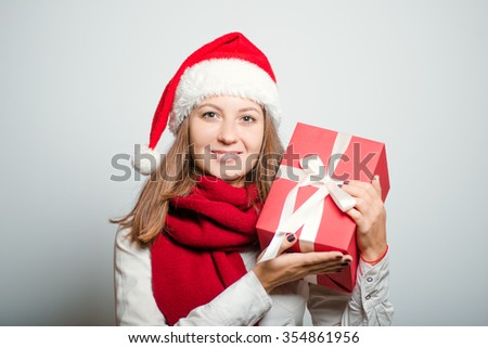 Santa girl receives or gives a New Year's gift. Christmas hat isolated portrait of a woman on a gray background, studio photo.