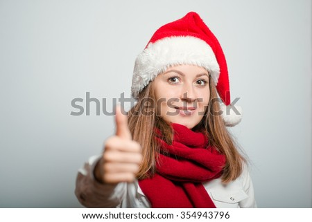Santa girl showing thumbs up, everything is OK. Christmas hat isolated portrait of a woman on a gray background, studio photo.