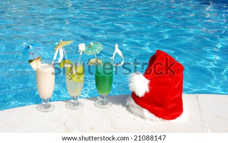 Santa hat and cocktails near the swimming pool - stock photo