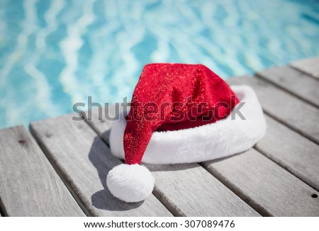 Santa hat by the swimming pool - stock photo