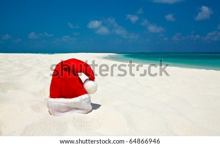 Santa hat is on infinity coral sandy beach - stock photo