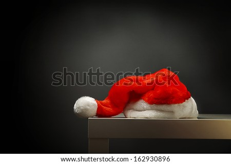 Santa hat laying on table against black background - stock photo