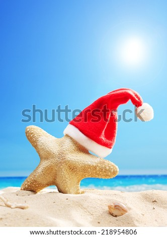 Santa hat on a starfish at a beach on a sunny summer day - stock photo