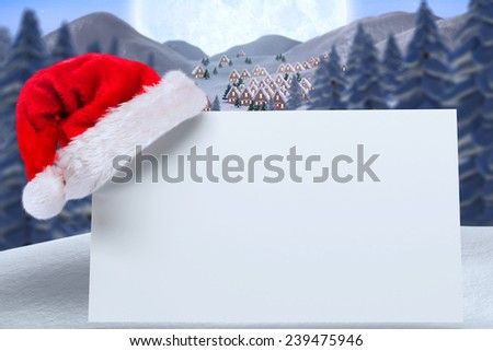 Santa hat on poster against cute christmas village under huge full moon - stock photo