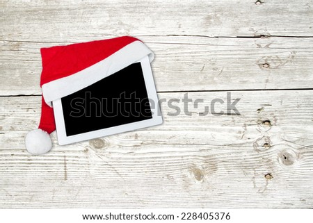 Santa hat on wooden table and tablet - stock photo