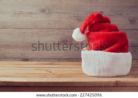 Santa hat on wooden table with copy space - stock photo