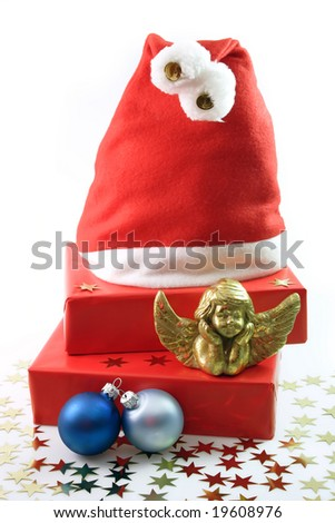 Santa Hat, red presents, golden angel figure, blue chrismas tree balls on light background - stock photo