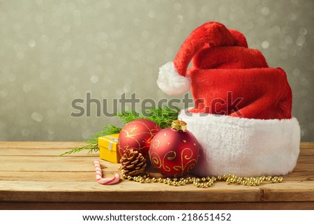 Santa Hat with Christmas decorations on wooden table - stock photo
