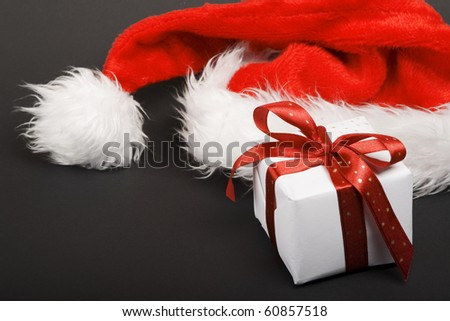 Santa hat with gift. - stock photo