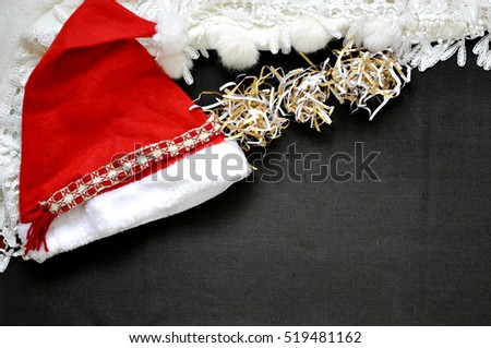 Santa hat with white scarf on dark brown fabric background for text