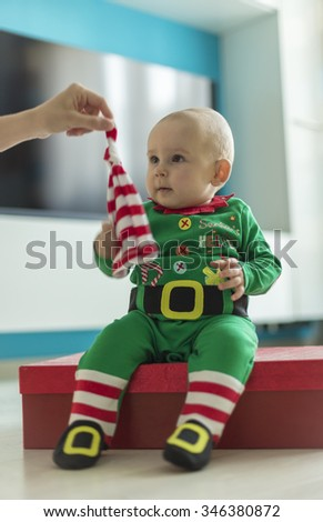 santa helper baby with red gift daytime - stock photo