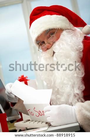 Santa holding Christmas letter and looking at camera - stock photo