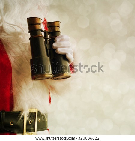 Santa holding hand binoculars - stock photo