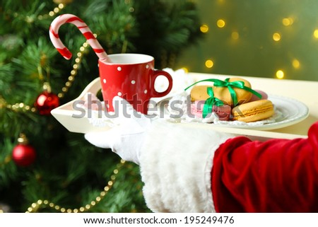 Santa holding mug and plate with cookies in his hand, on bright background - stock photo