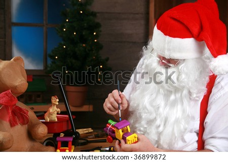 Santa in his workshop making new toys for Christmas Presents for children around the world - stock photo