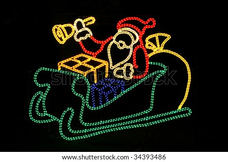 santa in sled outdoor holiday decoration with lights - stock photo