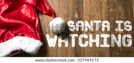 Santa is Watching written on wooden background with Santa Hat - stock photo