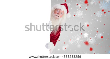 Santa looks out behind a wall against snowflake pattern - stock photo