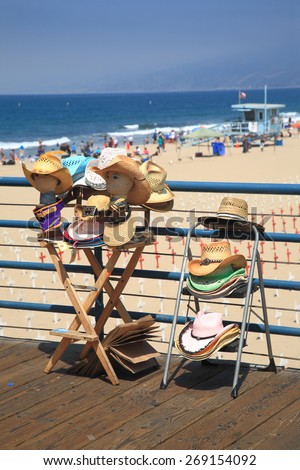 SANTA MONICA, CALIFORNIA - JULY 1: A display selling beach hats on the Santa Monica Pier on July 1, 2012 in Santa Monica, California. The pier opened in 1909 and now has an aquarium and a carousel. - stock photo