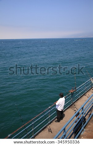 SANTA MONICA, CALIFORNIA - JULY 1: Fishing from the pier on July 1, 2012 in Santa Monica, California. The city has 3.5 miles of beach locations and averages 340 days of sunshine every year. - stock photo