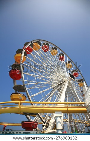SANTA MONICA, CALIFORNIA - JULY 1: Pacific Park on the Santa Monica pier on July 1, 2012 in Santa Monica, California. The park opened on 1996 and has the world's only solar powered Ferris wheel. - stock photo