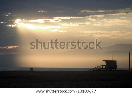 Santa Monica, California lifeguard stand with the sun bursting through the clouds - stock photo