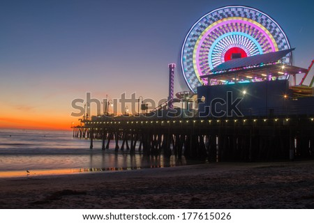 Santa Monica, California,  Pier Sunset 1. Angled view includes ocean, sand, Santa Monica pier, lit ferris wheel, and orange sunset. - stock photo
