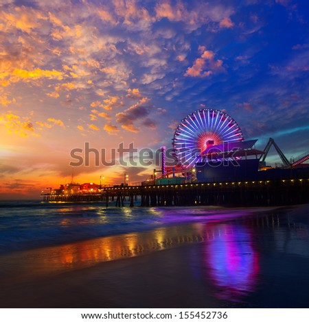 Santa Monica California sunset on Pier Ferris wheel and reflection on beach wet sand - stock photo