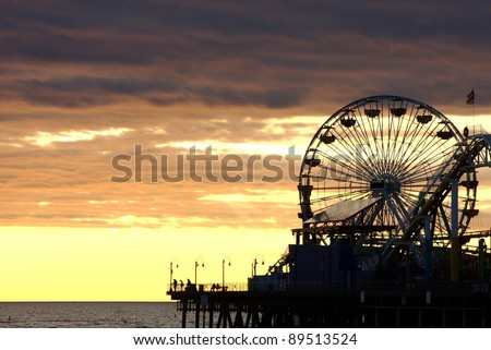 Santa Monica Ferris Wheel and Roller-coaster at Sunset - stock photo
