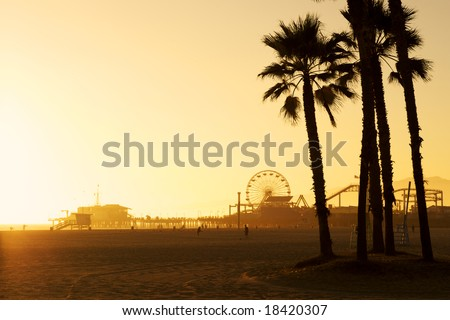 Santa Monica Pier framed by silhouetted Palm trees at dusk. There is space in the top left of the photo for copy text - stock photo