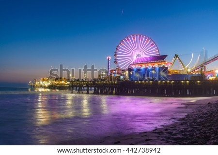 Santa Monica Pier illuminated with new lights at night. Beautiful reflection LED neon lights can be seen on the incoming waves.  - stock photo
