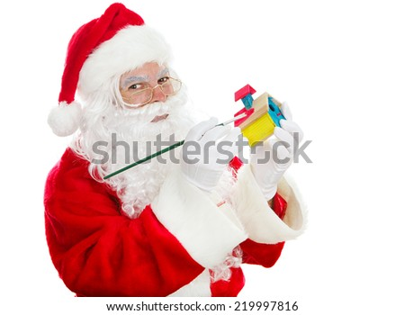 Santa painting a child's toy for Christmas.  Isolated on white.   - stock photo