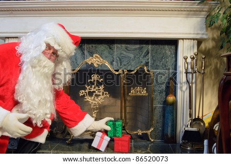 Santa placing some presents on the hearth looking surprised as he is caught doing it - stock photo
