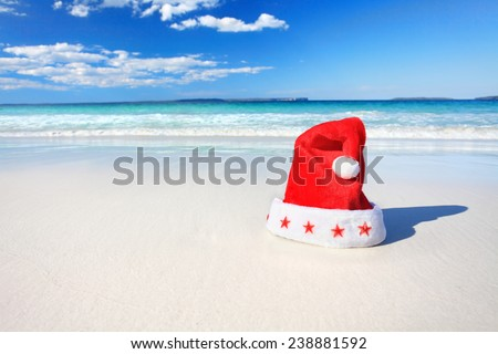 Santa red hat on a beautiful beach in summer.  Christmas downunder, Christmas or holiday vacation.  Shallow dof used with focus only to the fluffy red and white hat - stock photo