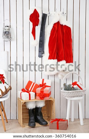 Santa red suit and gifts on a wooden white wall