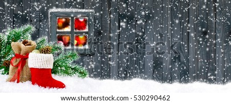 Santa's boot and bag with gifts and cones on wooden wall background and glowing lights outside the window