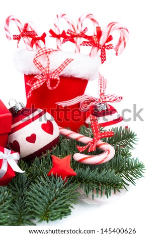 Santa's boot with candy canes and Christmas decorations on white background - stock photo