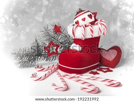 Santa's boot with candy canes and Xmas decorations on neutral gradient background, space  - stock photo