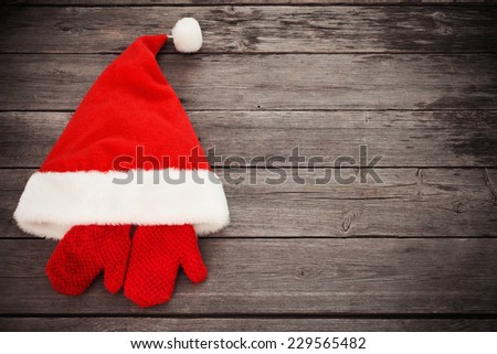 Santa's hat and red mitten on old wooden background - stock photo