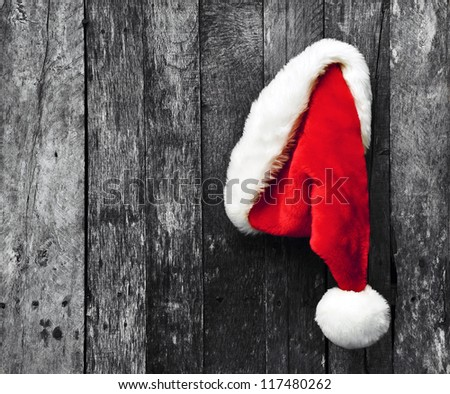 Santa's hat hanging on a desaturated grunge wood background. - stock photo
