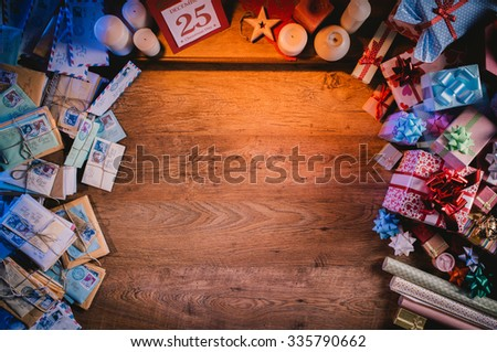 Santa's wooden Christmas desktop with gifts, letters and wrapping paper, top view, copy space at center - stock photo