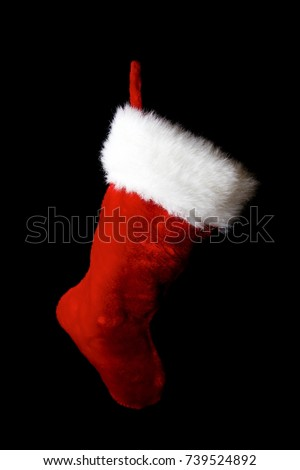 Santa sack/stocking in the shape of Santa's boot. Red, white and fluffy. Black background. Low key