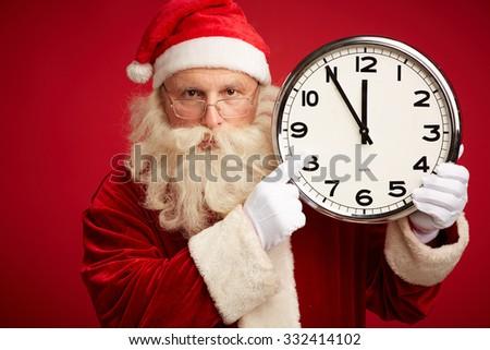 Santa showing at clock before Christmas night - stock photo