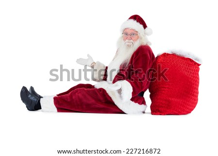 Santa sits leaned on his bag and has no clue on white background - stock photo
