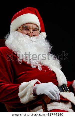 Santa sitting and smiling isolated on black - stock photo